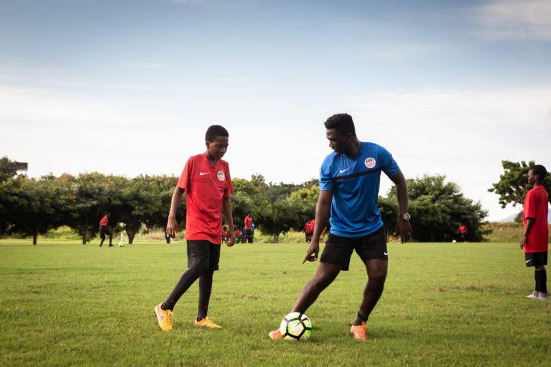 King Gyan plays soccer with one of his students.