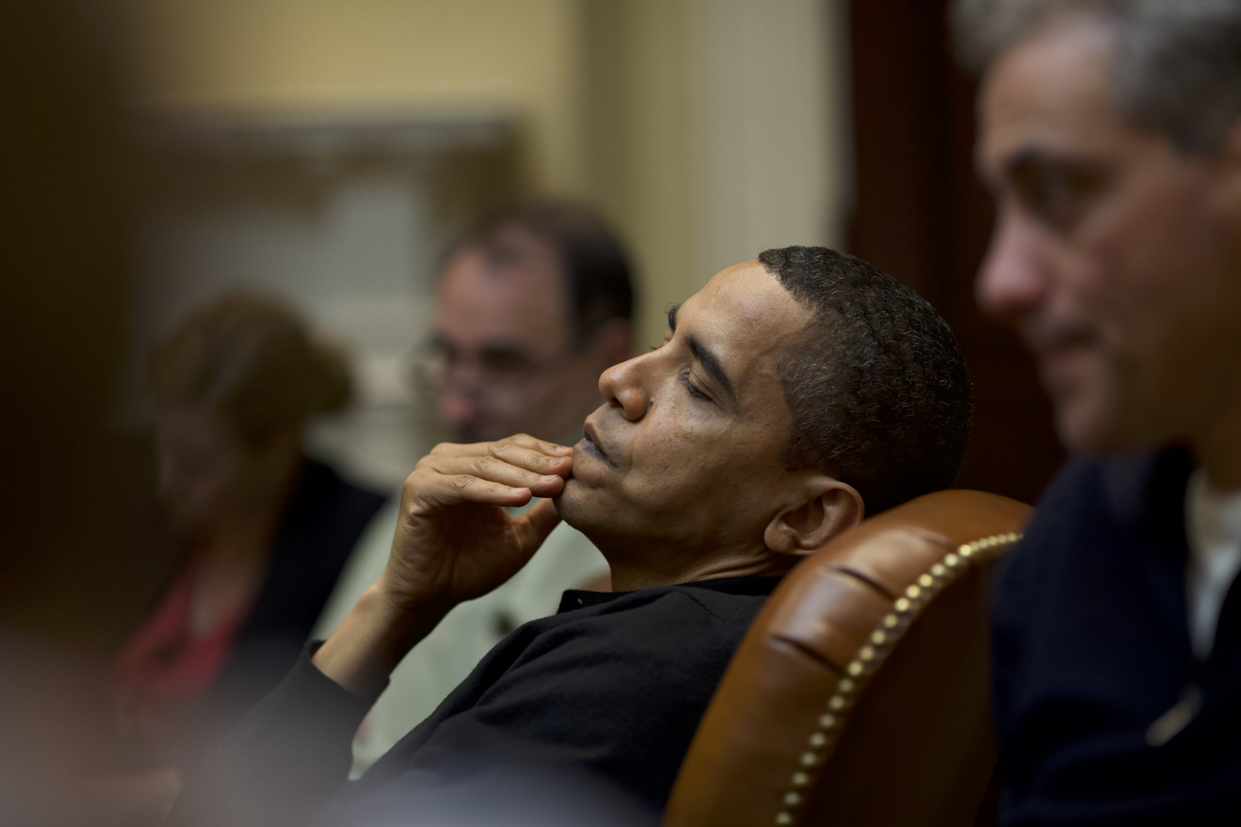 President Obama leans back in his chair with a hand resting on his chin.