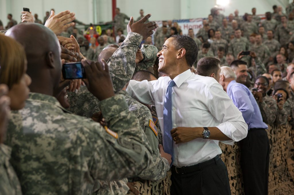 President Obama reaches to shake hands with a cheering crowd of American soldiers.