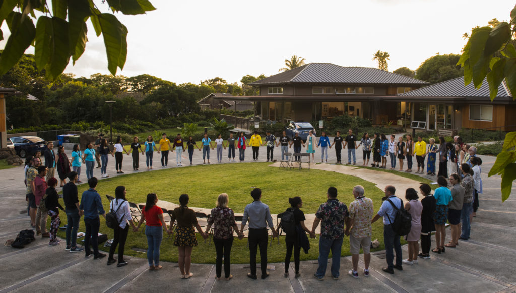 A group of people hold hands in a circular formation at dusk.
