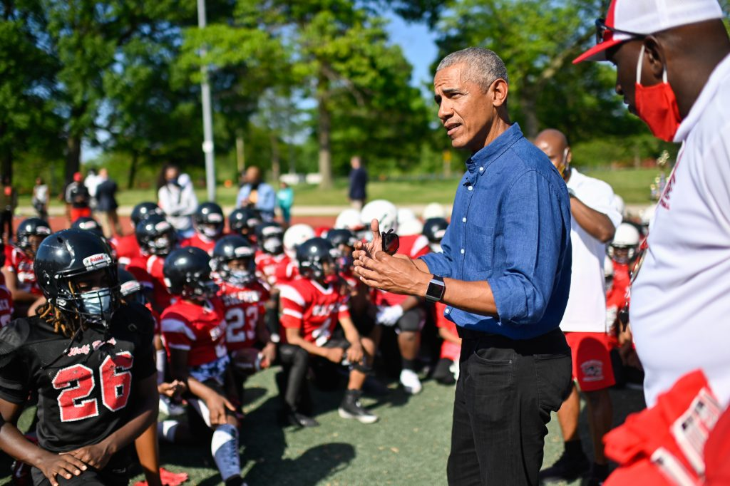 President Obama speaks to a youth football team. The players have taken a knee as President Obama gestures towards them.