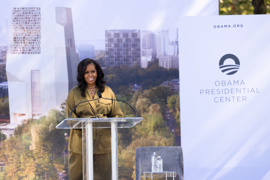 Former First Lady Michelle Obama smiles as she delivers remarks behind a podium.