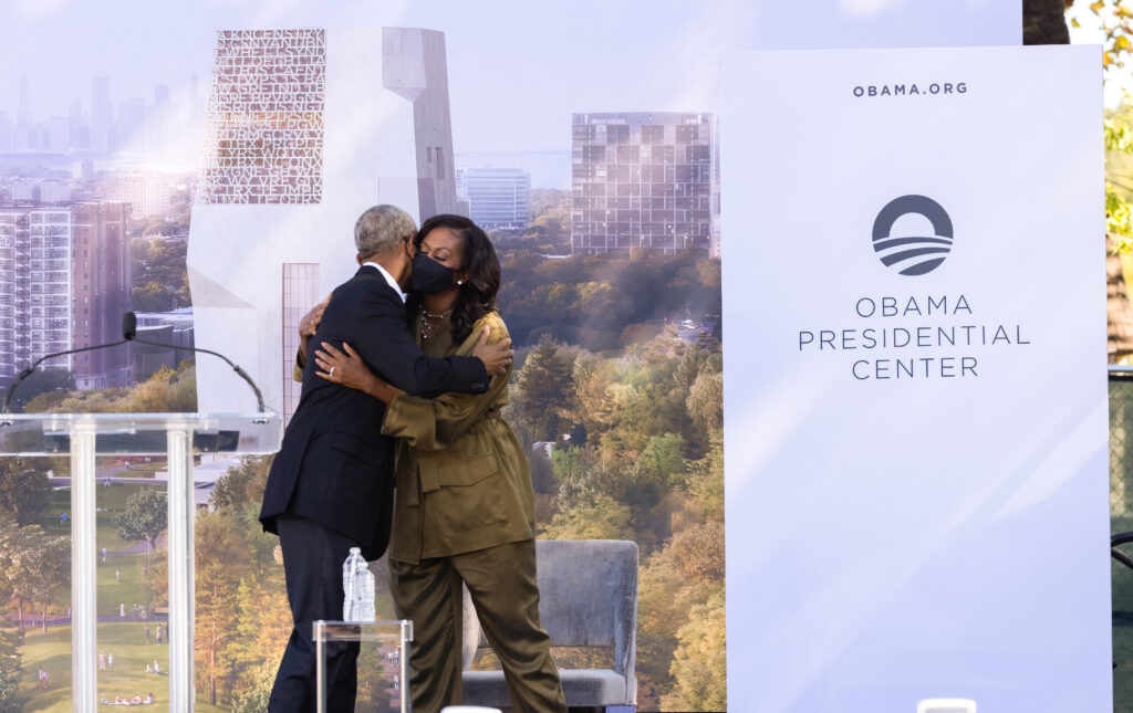 President Obama hugs former First Lady Michelle Obama at the groundbreaking event for the Obama Presidential Center.