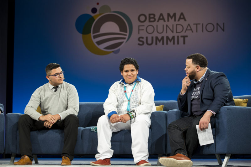 Three men sit on sofas in conversation in front of an Obama Foundation Summit logo