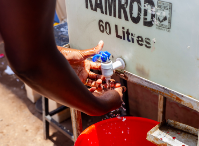 A person's hands are shown as they wash them at a hand washing station that Kennedy Odede set up.