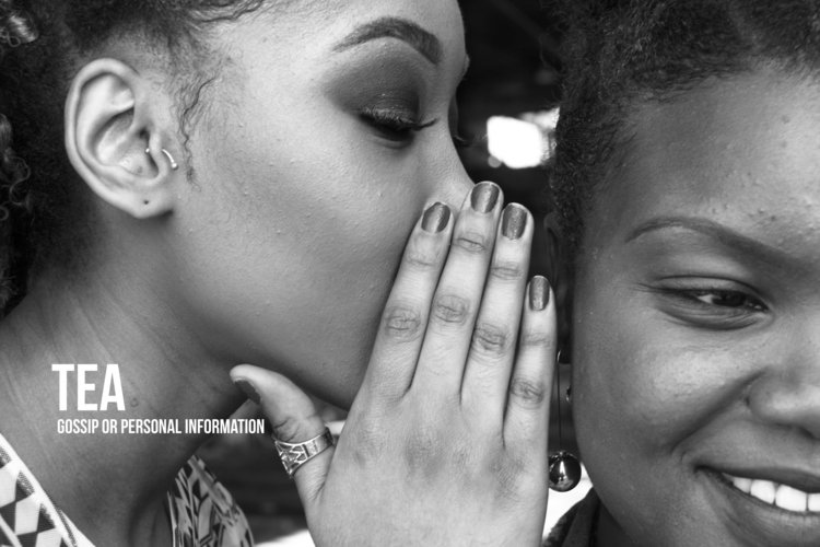 A Black woman whispers in the ear of another Black woman.