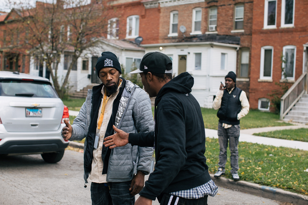 Two men in winter clothes greet each other on a residential Chicago street.