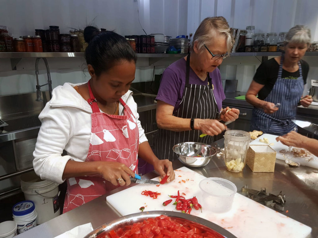 Three women work at a table chopping vegetables for preserving.