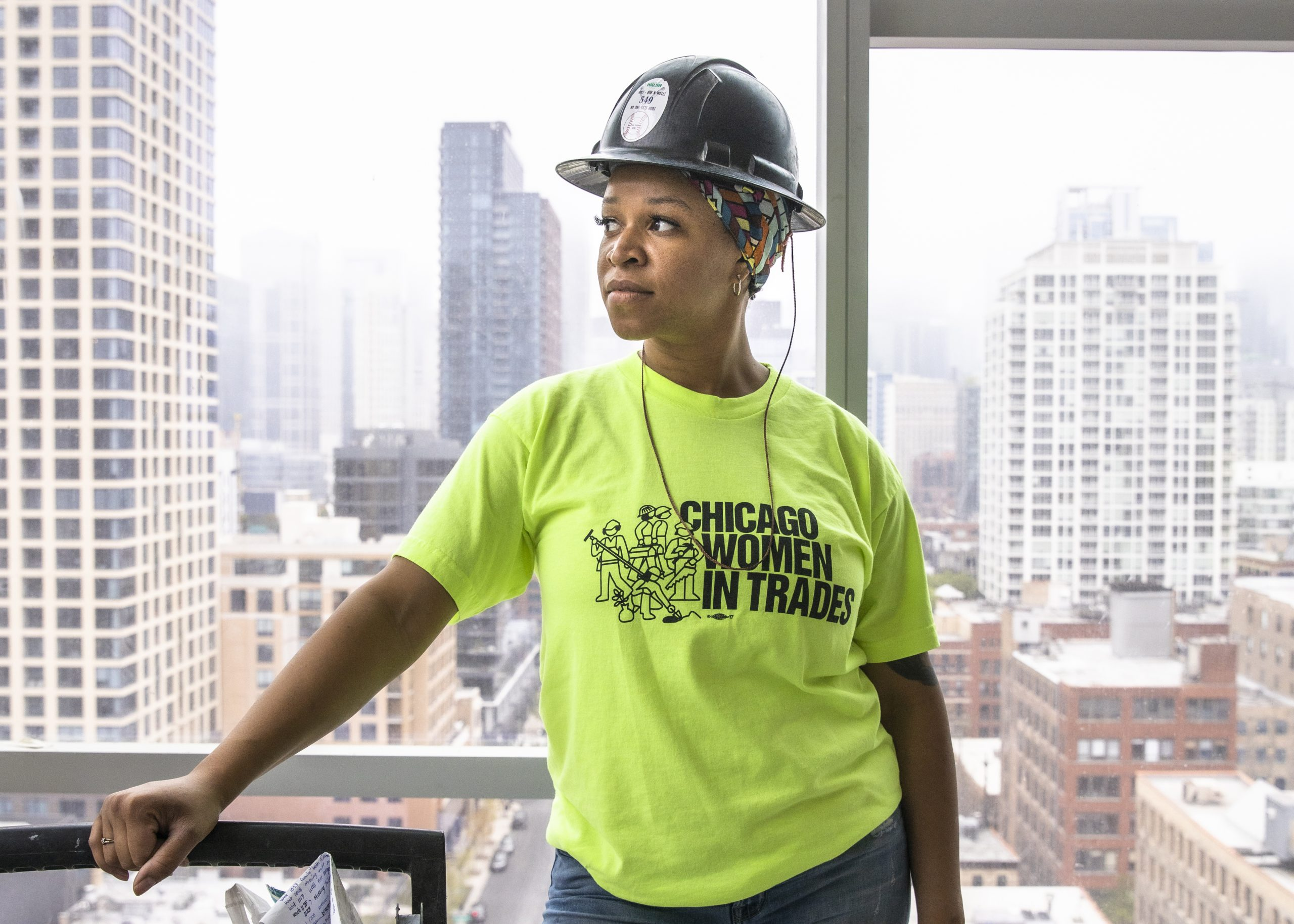 Zahrah Hill looks to the horizon wearing a hard hat and neon green shirt.