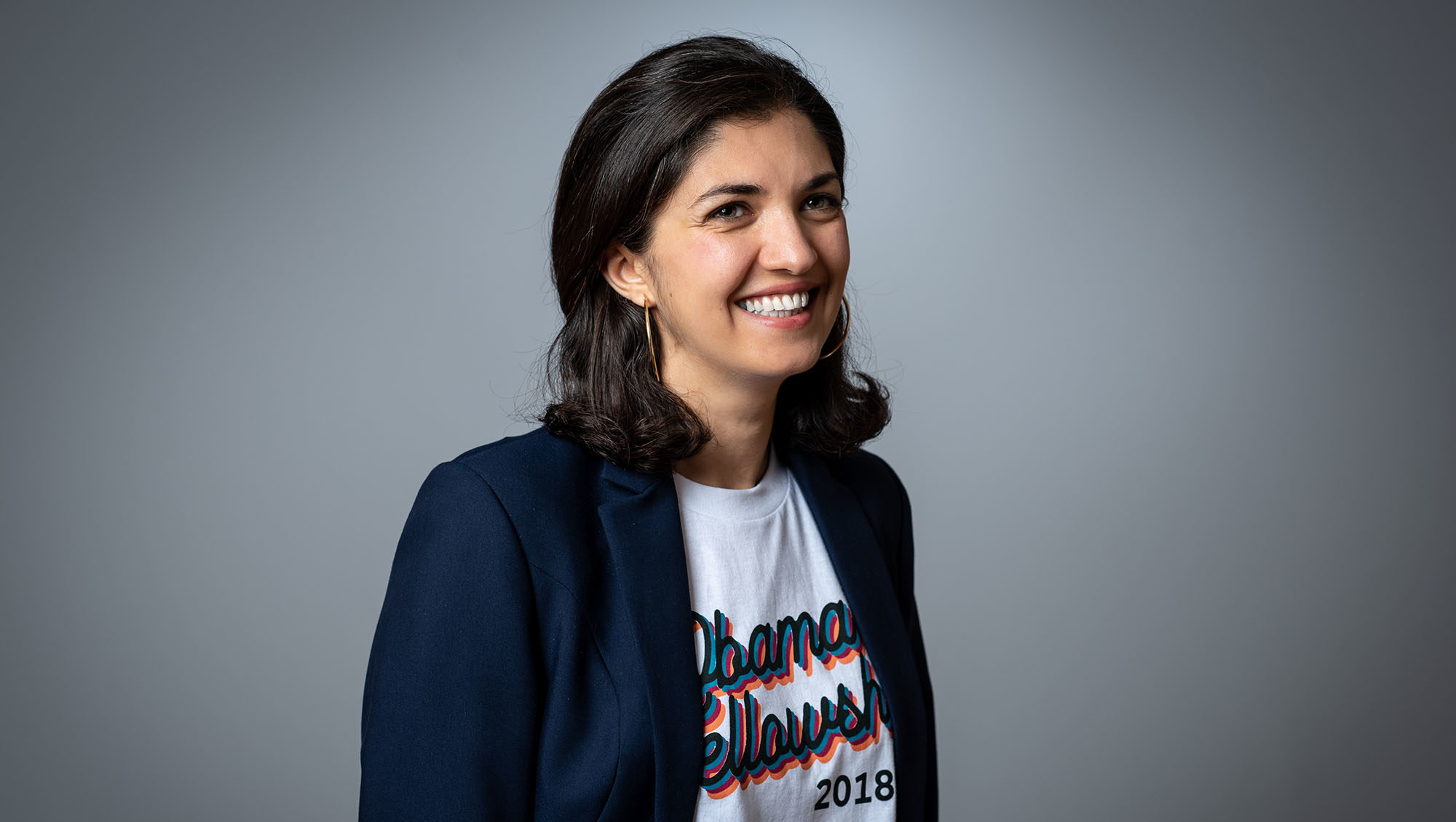 Zarlasht smiles off-camera wearing an Obama Fellowship t-shirt and blazer.