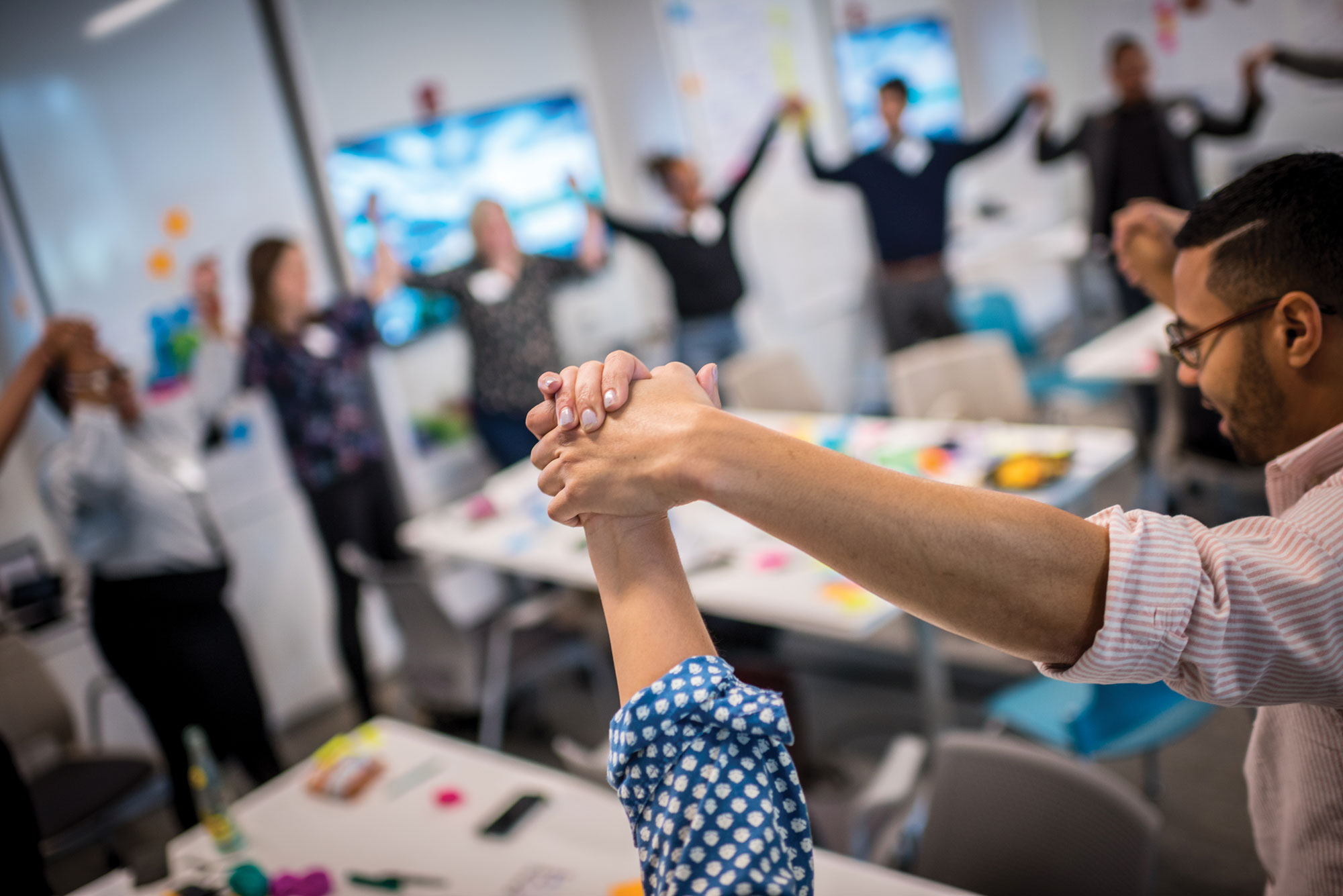 Two program participants holding hands during a workshop session.