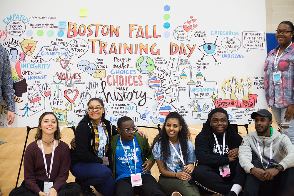 A group of participants pose in front of a board of vidual notes at the Obama Foundation Pilot Training Day in Boston.