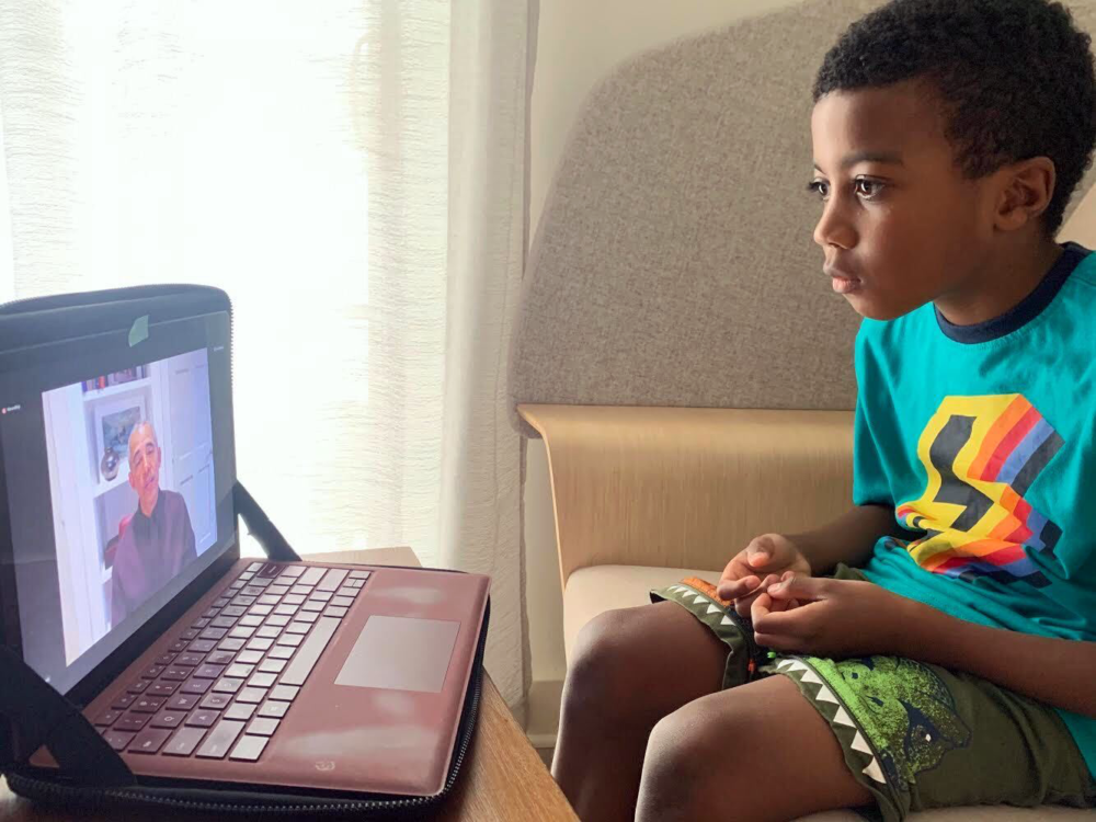 A young boy watches President Obama on a laptop during a Obama Foundation town hall.