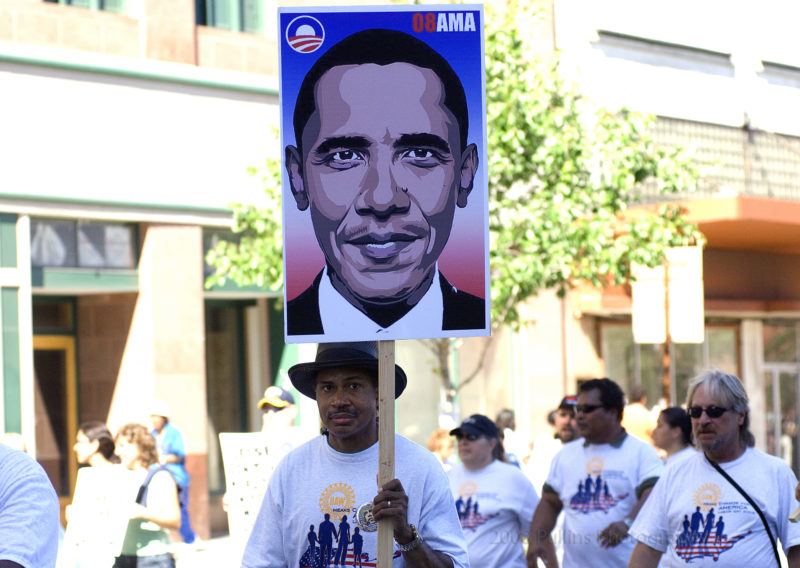 Man wearing a black hat carries a sign with a photo of then-Senator Obama in 2008.